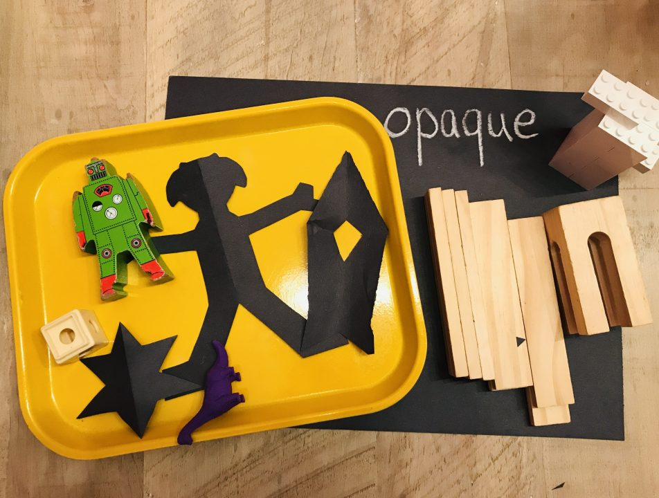 """An arrangement of materials on a piece of black paper and a tray. The materials include paper cutouts, wood blocks, LEGO bricks, and a toy dinosaur. The paper reads """"opaque."""""""