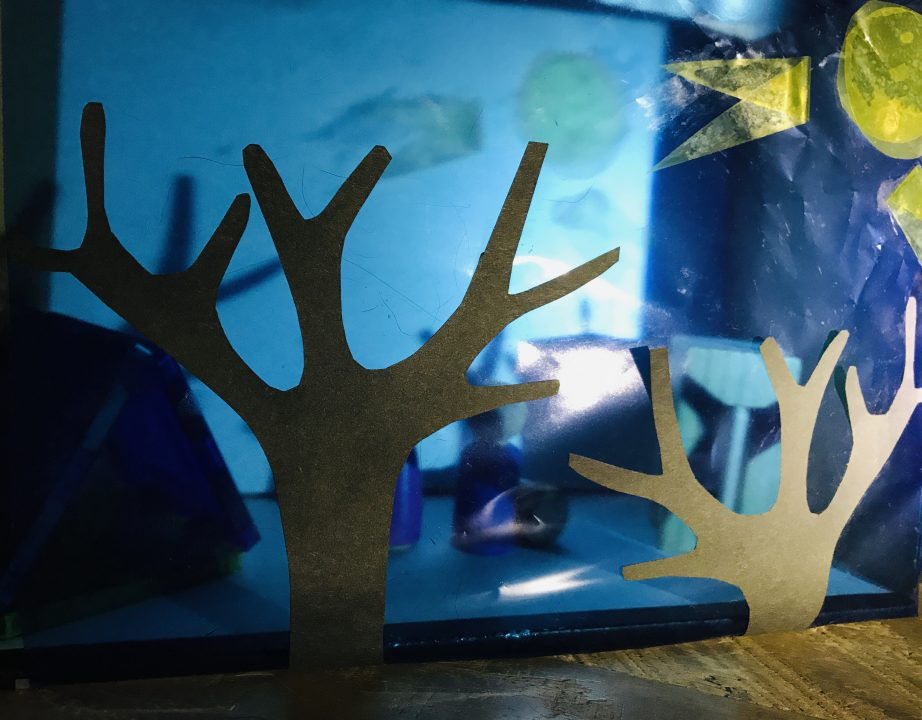 A shoebox shadowbox features a screen of translucent blue with black tree silhouette cutouts. Inside the box are small figures and a triangular structure. Shadows are cast on the back of the shoebox.