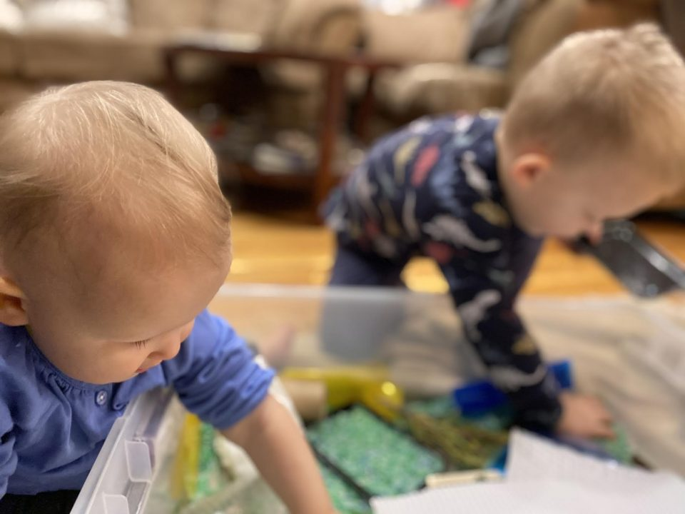 Two toddlers lean over a large bin filled with loose green, yellow, and blue materials. Each child has one hand inside the bin, and their faces look in toward the materials.