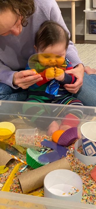 A baby sits on a woman's lap in front of a sensory bin. The woman holds a yellow transparent circle in front of his face; the baby grasps a blue crinkly material.