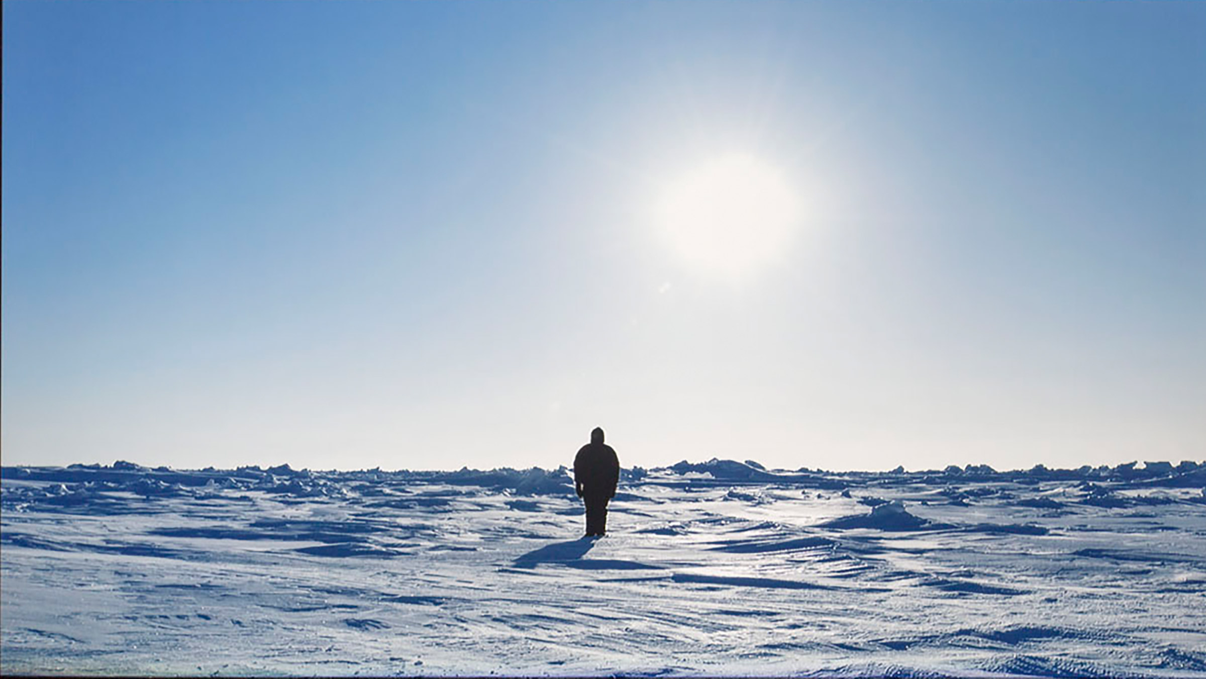 Person standing in a snowy landscape facing the sun