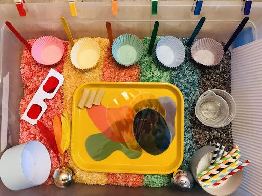 Bird's-eye view of a sensory bin. Inside, rice and other materials are arranged in rainbow order. Materials include popsicle sticks, baking papers, feathers, and straws—all in multiple colors—as well as clear cups, and a yellow tray holding colorful shape cutouts.