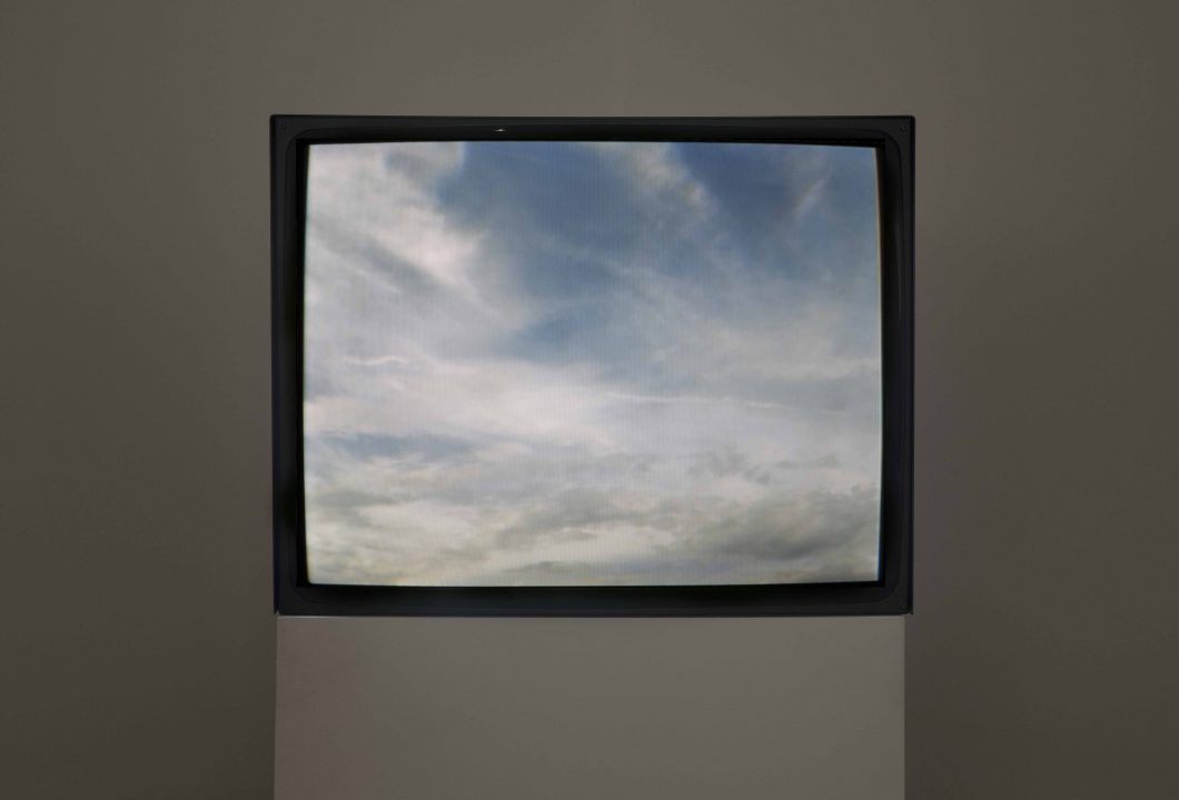 A TV screen on a pedestal shows image of the sky